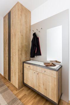 garderobenpaneel mit 5 kleiderhaken oberhalb eines an diesem paneel hangenden sideboards im flur rechts neben