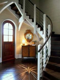 Front foyer with circular staircase...inlaid center medallion wood floors, rounded top door. All of it..I'm in love!