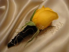 Boutonniere designed with a yellow rose wrapped in satin and gold wiring.