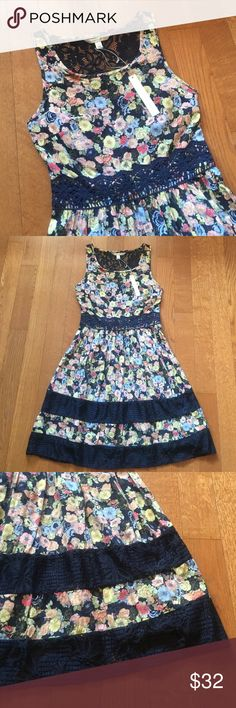 NWT Lauren Conrad lace accent dress Lace trim racer back dress. Main color is navy with floral pattern. Lace accent to waist, upper back, and bottom of dress. See sizes available, new with tags. LC Lauren Conrad Dresses