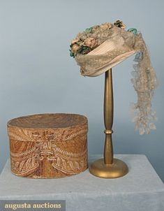 Wedding bonnet and original box, c1860; White straw small brimmed hat trimmed with aqua & pink cloth roses and blonde lace, in small oval hand decorated box in rust & white