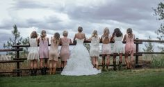 Matt Shumate Photography at The Ridge at Rivermere wedding venue bride and bridemaids portrait standing along a fence, cloudy skies, pink lacy dresses cowboy boots