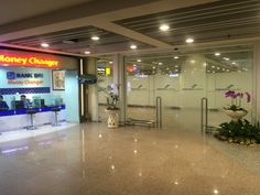 bali airport arrivals hall. these are the doors that you will walk through after you have cleared customes. there is a money changer on your right hand side. money changers in the airport offer considerably lower rates.