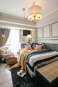 From the entryway, visitors can see the entire unit. A chandelier with fabric shade gives the space an elegant feel while one can instantly feel at home the moment they set eyes on the bed. To define this part of the home, a shag rug from H&M Home was also added.