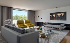 House tour: a sleek apartment in Portugal : In the living room, the yellow armchairs are by Munna, the table lamp is 'Taccia' by Flos, the floor lamp is 'Sinatra' by Delightfull, the day bed is the iconic 'Barcelona' by Ludwig Mies van der Rohe, and the Carrara marble low tables are by Pierro Lissoni for Living Divani. Vintage ceramic pots decorate the coffee table.