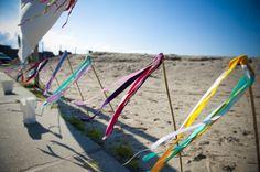 Leuke aankleding voor een strand huwelijk. Houten stokken met gekleurde linten en de wind die daar doorheen blaast!