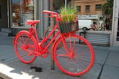 Deko auf der Straße - Fahrrad gestreicht in fluoreszierender Farbe Orange Rot