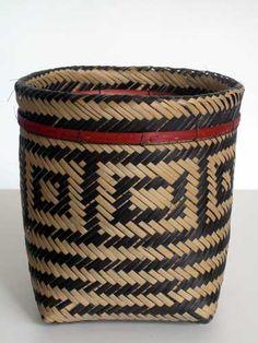 Arte indígena brasileira. Cesto paneiriforme ou urutu, elaborado em fibra de arumã trançada nas cores preto e natural, aro plano com tingimento em vermelho.