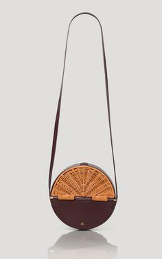 Round cross-body bag in Italian vegetable-tanned calf leather. Custom wicker front panel made in the Philippines with magentic closure. #rachelcomey