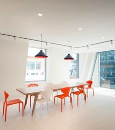 This white meeting room provides a real blank canvas for brainstorming meetings. Natural light floods the room from the full length windows. The room gets a funky feel from orange and black pendant lights and different styles of orange and white chairs around a wooden table.