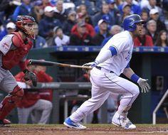 Kansas City Royals' Alex Gordon (4) follows through on a sacrifice fly in front of Cincinnati Reds catcher Tucker Barnhart (16) that scored Eric Hosmer in the second inning during Wednesday's baseball game on May 20, 2015 at Kauffman Stadium in Kansas City, Mo.
