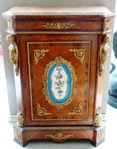 Dunquerque estilo Luis XV, de madeira nobre encascada em raiz, porta decorada centralmente com placa de porcelana de Sevres, quinas chanfradas com figuras híbridas de bronze dourado, assim como frisos filetes e apliques. 78 x 83 x 115 cm altura.
