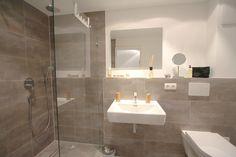 Stylisches Badezimmer in Betonoptik mit Raindance Dusche.