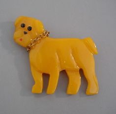 Cute yellow Shultz Bakelite carved bulldog brooch with chain collar.