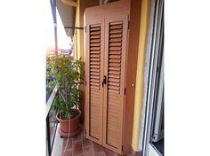 Fotografia di un armadio a 2 ante colore PKA8 ciliegio chiaro, con doghe orientabili nella parte superiore e doghe chiuse nella parte inferiore