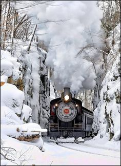 Beautiful Nature.Train chugging and steaming along through walls of trees covered in snow.