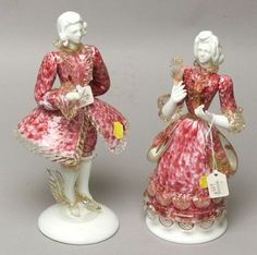 Pair of Venetian Glass Figures of a Lady and Gentleman, mid 20th century, both in eighteenth century dress, white glass faces and arms, with mottled white, cranberry, and blue flecked clothes, accented with colorless gold flecked trim, man ht. 11 5/8, lady 10 7/8 in.