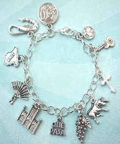 this charm bracelet features spain inspired Tibetan silver charms (nickel free). the charms are attached to a silver tone 7.5 inches chain bracelet.