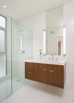 The floating vanity in this small bathroom continues the trend of zebra wood and white countertop throughout the home. The mirror and the light fixtures also mirror the ones in the master bathroom. This gives the home the feeling of continuity throughout. See it at hgtv.com.