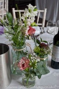 Different size jam jars are stuffed with English country garden style flowers and foliage and grouped together to form an elegant wedding table centrepiece.