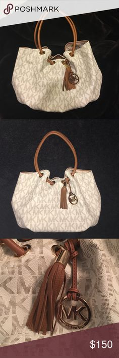 Michael Kors Medium East West Ring Tote This Michael Kors mid-size East West Ring Tote in Signature Vanilla is wrapped in Michael Kors monogram block print on jacquard fabric and trimmed in off-white vanilla leather. It is accented with polished golden hardware including the removable Kors circular hanging charm on the front, and oversized tassel. It is lined in Kors monogram printed fabric and features a zippered pocket and (4) open slip pockets. It has an open top with a tab and magnetic…