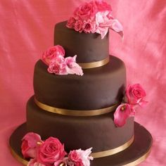 Three tier chocolate wedding cake with a gold ribbon around each layer and decorated with pink flowers.