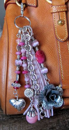 This handmade tassel charm can be used on your purse, backpack, zipper, wherever youd like to add some charm! Its made up of silver plated chain, an antiqued silver plated flower charm, a silver toned heart charm, and agate, glass, and silver beads. The suede tassel is a beautiful light pink color. It is approximately 6.75 long.