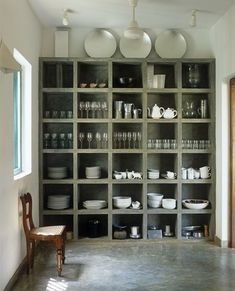 Beautiful modern minimalist kitchen storage idea - concrete shelves and floors, with white ceramics and silver plates