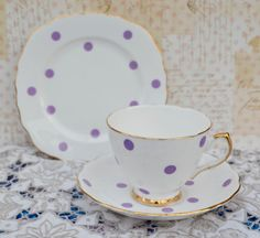 Vintage bone china tea trio made by English china company Royal Vale, likely manufacture date 1940s- 1950s. The trio consists of tea cup, saucer, tea plate in white china decorated with lilac/lavender polka dots and trimmed with gilding to the rims of the china and also on the foot and handle of the tea cup. The china is in very good vintage condition free from chips, cracks, crazing, stains and the gilding is bright with some rubbing. As with all vintage items age and usage related wear is…