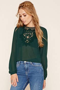 A semi-sheer chiffon woven top featuring ornate crochet trim on the front, a round neckline, long cuffed sleeves, and a top button closure in the back.