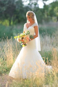 cap sleeved wedding gown   lovely portraits in field. Enough color in bouquet which pulls greens from the landscape to be beautiful in photography.