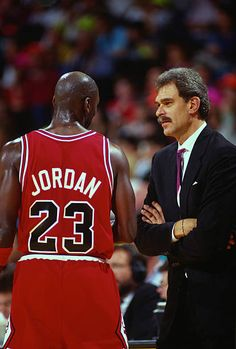 Michael Jordan of the Chicago Bulls talks with head coach Phil Jackson against the Washington Bullets during an NBA basketball game circa 1990 at the...