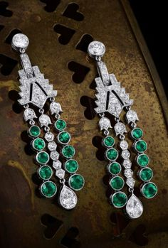 A pair of Art Deco platinum, diamond and emerald earrings.