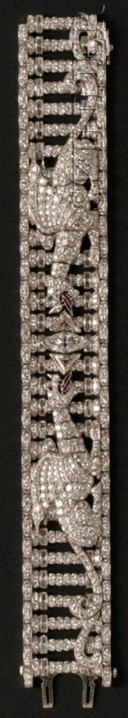 A Fine Art Deco Platinum and Diamond Figural Bracelet, Retailed by Thomas Kirkpatrick, & Co., New York. Designed as a colonnade with two horned winged dragons breathing calibré-cut ruby fire, centring a marquise-cut diamond, triangular-cut diamonds, and further set with baguette-, full-, and single-cut diamonds, numbered with American marks, unsigned. #ArtDeco #bracelet