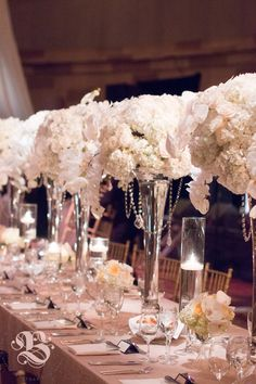 Ethereal wedding table centerpieces at Gotham Hall in Manhattan: white hydrangea and Phalaenopsis orchids, cream Vendela and Creme de la Creme roses, in alternating high and low glass vases with hanging crystals, illuminated by glass-stemmed floating candles. Photo by Jasmine Hsu. #weddingflowers