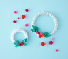 Mini Wreaths Wrap pipe cleaners around an embroidery hoop and embellish with pom poms and felt leaves.