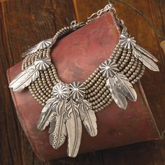 Antiqued sterling silver feathers caught by vintage-style buttons on a line-up of beaded strands.