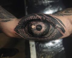 Black and grey style eye tattoo on the right inner arm.