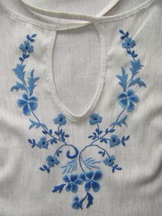 12. White top with dark and light blue embroidery design