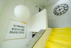 Murowane schody z minimalistyczną barierką nabrały wyrazu dzięki żółtej farbie do betonu. By nie wprowadzać chaosu kolorystycznego, a jednak zachować ozdobną strukturę, ceglaną ścianę na piętrze pobielono. Jest dobrym tłem dla zegara w industrialnym stylu.