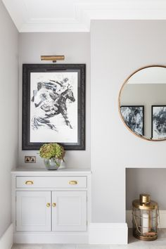 Light gray cabinetry on either side of the fireplace + art piece with picture light above + brass hardware + round mirror over the fireplace Empty Fireplace Ideas, Fireplace Art, Dining Room Fireplace, Unused Fireplace, Christmas Fireplace, Fireplaces, Christmas Decor, Alcove Storage, Dining Room Storage