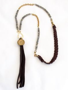 Amazing collection of soft Colorado hand-woven chocolate deerskin, chocolate deerskin tassel, stranded faceted Labradorite, vintage brass links and a vintage French prayer coin.