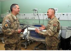 Command Senior Chief Hospital Corpsman James Fyfe discusses patient care with Hospital Corpsman 2nd Class Larry Bullard at the Role 3 Multinational Medical Unit (MMU) based at Kandahar Airfield. Approximately 90 Navy Reserve and Active Duty Sailors and Officers work at the MMU, which is the primary trauma receiving and referral center for all combat casualties in Southern Afghanistan and is manned largely by individual augmentee personnel serving on the NATO-led mission Resolute Support.