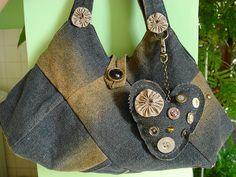Confeccionada com retalhos de velhos jeans reciclados . Enfeitada com fuxicos, acompanha chaveiro  com botões vintage. O botão do fechamento da bolsa é de uma roupa comprada em N.York há mais de 14 anos.