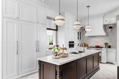 Modern kitchen with wall of white cabinetry and island with white marble countertop