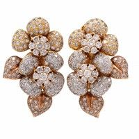 These estate diamond cluster  earrings of flexible design are crafted in  solid 18K yellow gold, weighing approx: 31.3 grams and measuring approx: 37.5mm high x 22.5mm wide. Designed in a beautiful display of leaves and flower motif completely embellished with genuine round cut diamonds in prong setting, weighing approx: 5.98cttw and graded H-I color,  VS clarity. These stunning earrings feature posts and clip-on, designed for pierced and non-pierced ears, and remain in excellent condition.