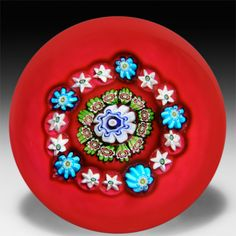 Antique Clichy rare red ground spaced concentric millefiori glass paperweight. by  Clichy