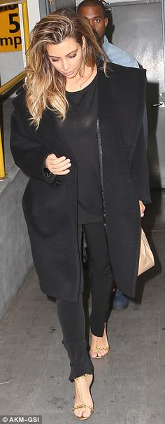 All black: Kim looked striking in an all-black ensemble that she paired with a pair of leopard open toe strappy heels
