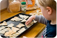 """Pita Chips-use a pizza cutter to cut """"chip shapes"""" and have kids arrange them on a tray as close as possible but not overlapping! Spritz with olive oil, salt and herbs, Bake at 100* for 10 minutes."""