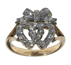 A twin Diamond Heart Ring, English c.1880        A Victorian period ring Formed by two diamond set hearts and diamond set ribbon above, to the bifurcated shoulders, close set in silver and gold.    Weight: 4.8 gr